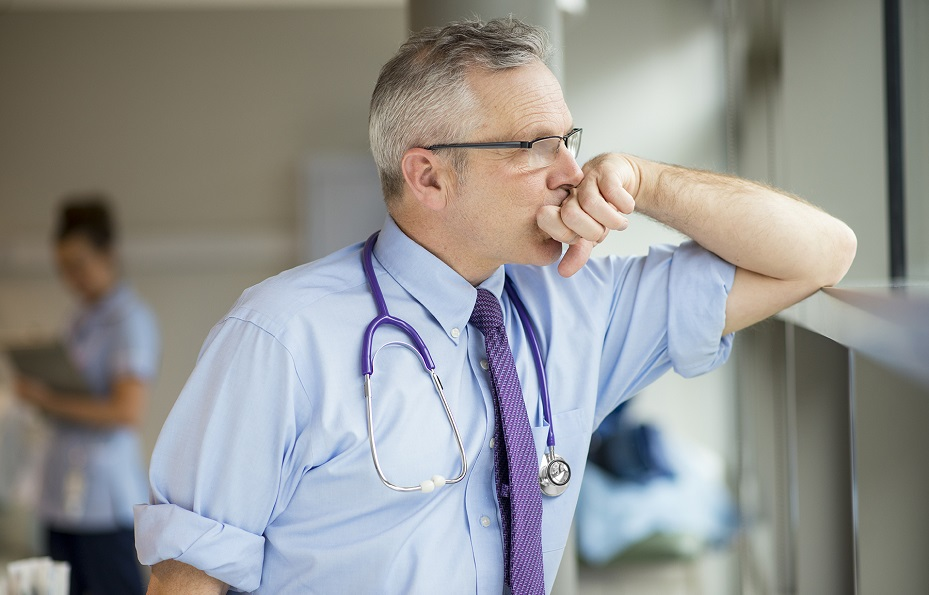 An exhausted doctor looks out of the window in a hospital. With 5thPort's digital and electronic informed consent process, this kind of clinician burnout can be greatly reduced.